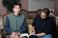 Young man reading with mentor